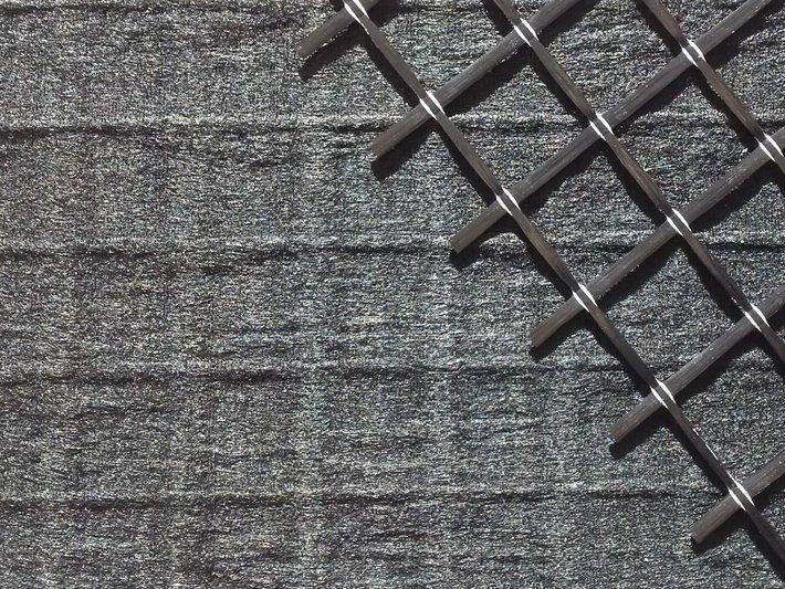 Carbon fiber nonwoven reinforced with carbon fiber grid